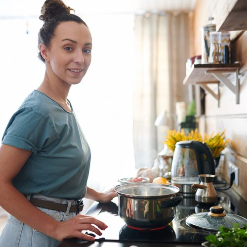 Young pretty housewife in t-shirt and jeans looking at you while standing by electric stove in the kitchen